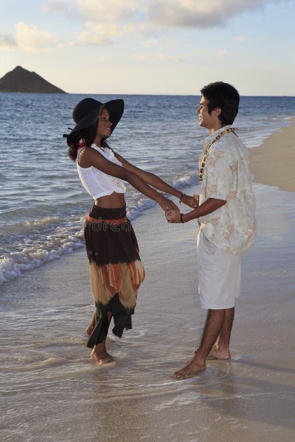 Jeunes couples de chemin mélangé à la plage photos libres de droits
