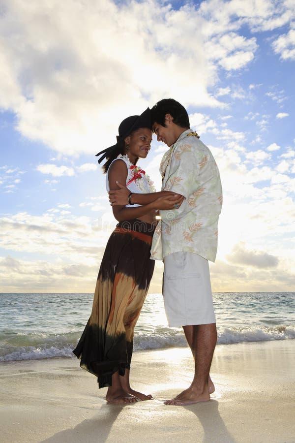 Jeunes couples de chemin mélangé à la plage photographie stock