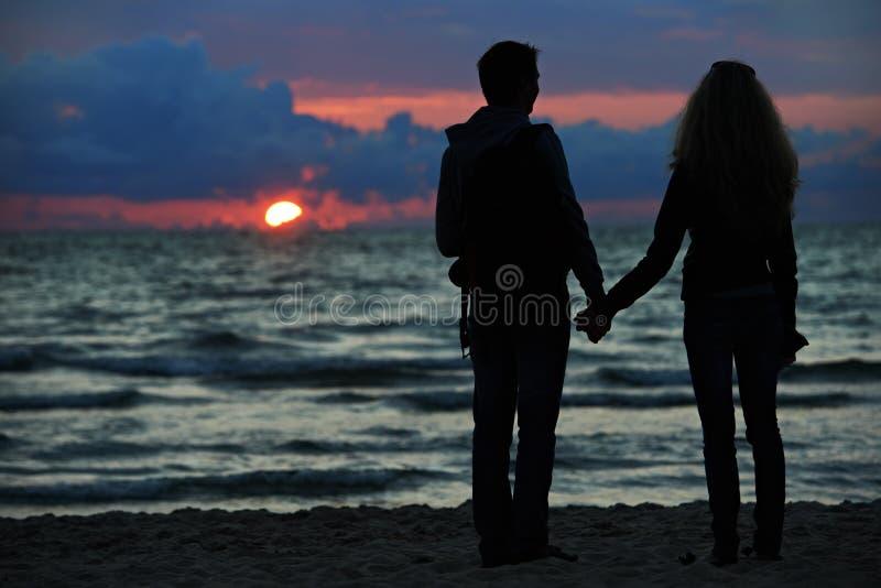 Jeunes couples de famille à la plage de coucher du soleil photos libres de droits