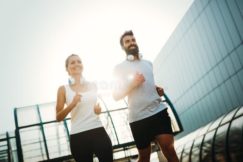 Jeunes couples de forme physique fonctionnant dans la zone urbaine photo stock