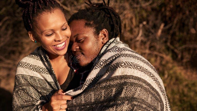 Jeunes couples de métis embrassant sous la couverture dehors pendant le coucher du soleil photos stock