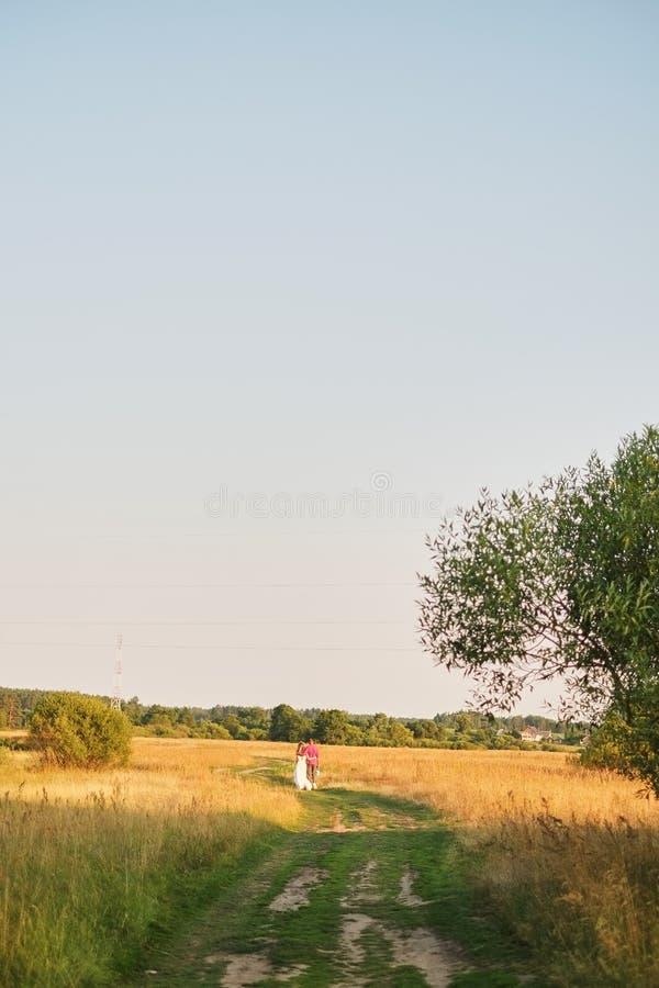 Jeunes couples de mariage marchant sur la zone Rétro type photos stock