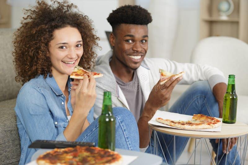 Jeunes couples de portrait mangeant de la pizza à la maison image stock