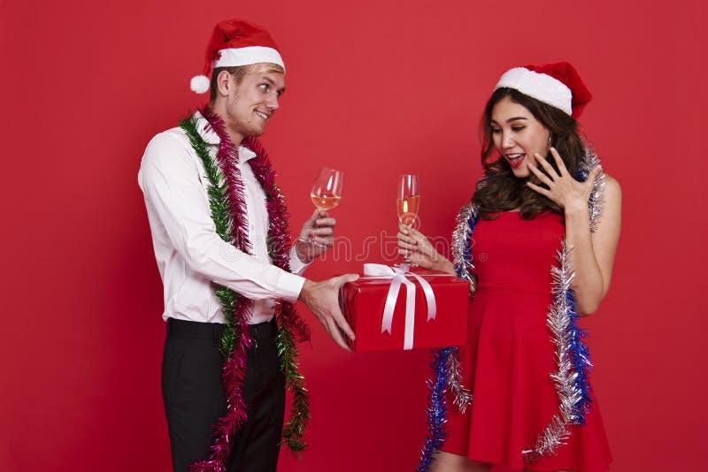 Jeunes couples de portrait tenant des verres de champagne et de boîte-cadeau photographie stock