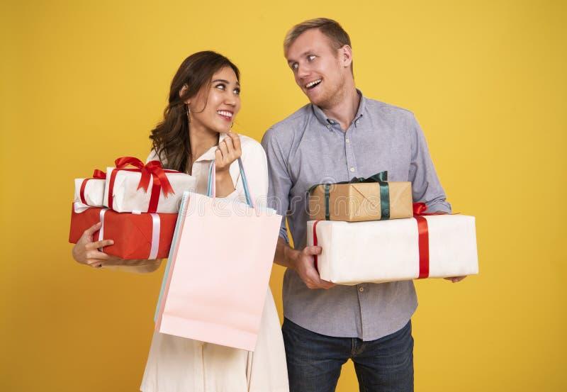 Jeunes couples de portrait tenant le sac de papier et le boîte-cadeau de achat images stock