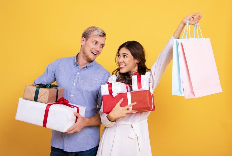Jeunes couples de portrait tenant le sac de papier et le boîte-cadeau de achat photo stock