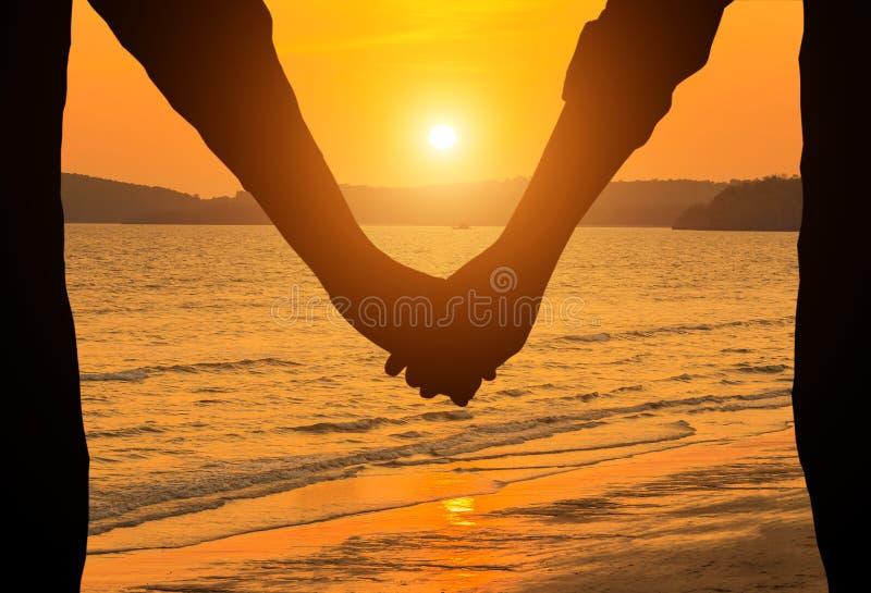 Jeunes couples de silhouette tenant des mains dans le coucher du soleil photos stock
