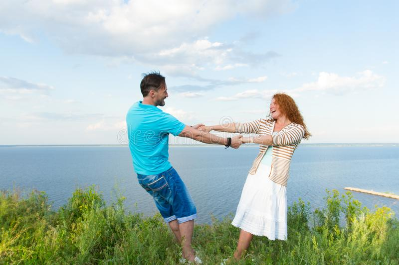 Jeunes couples de sourire aimants dans l'herbe sur le fond de lac et de ciel Tiré de la jeune danse rouge attrayante de femme de  images libres de droits