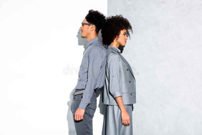 Jeunes couples de sourire amercian africains dans les costumes gris se tenant de nouveau au dos sur gris et blanc photos stock