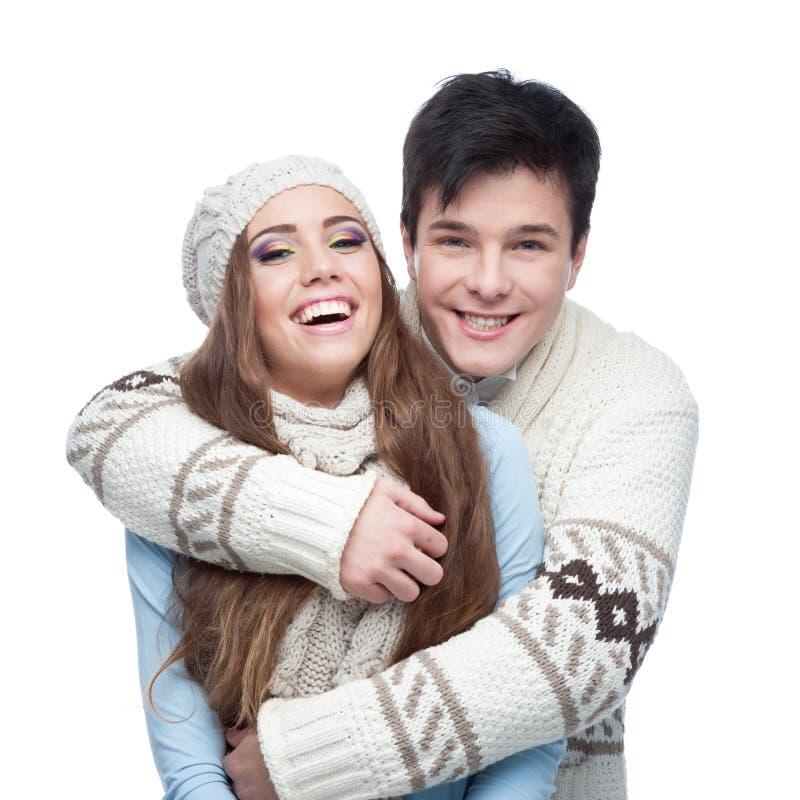 Jeunes couples de sourire dans l'embrassement d'habillement d'hiver images libres de droits