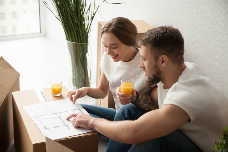Jeunes couples de sourire discutant le plan architectural de maison photographie stock