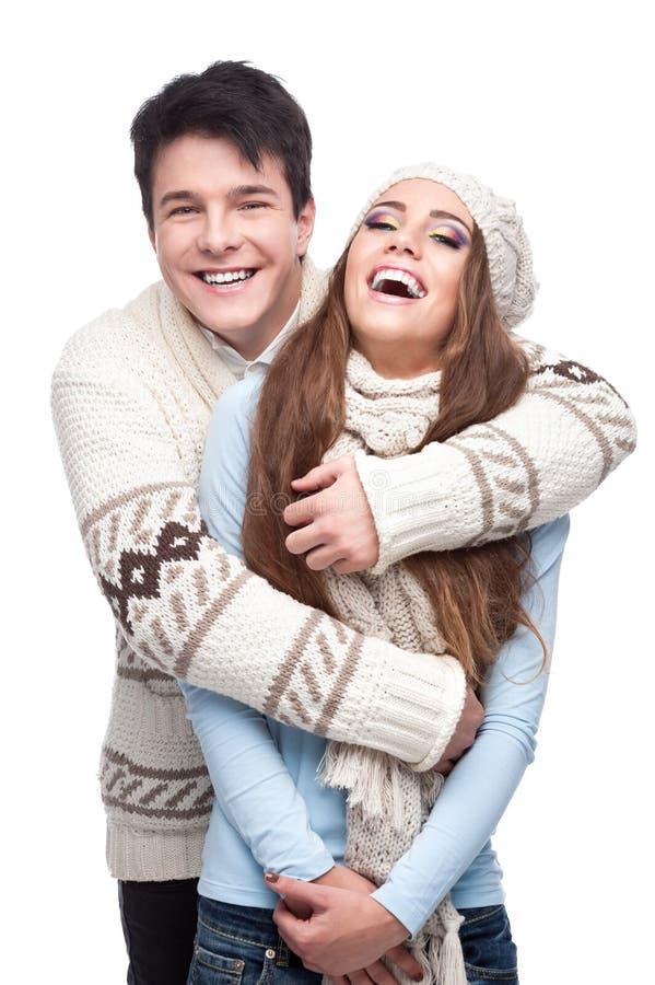 Jeunes couples de sourire en embrassement de vêtement de l'hiver photos stock