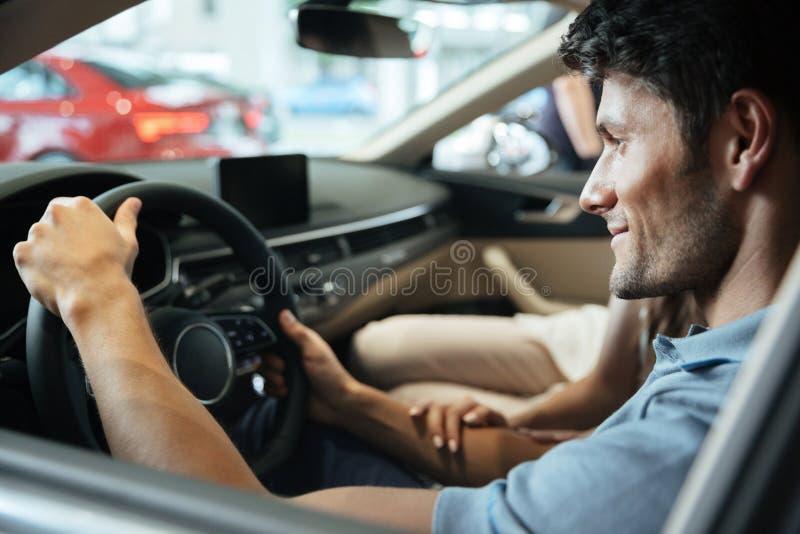 Jeunes couples de sourire examinant une nouvelle voiture images libres de droits