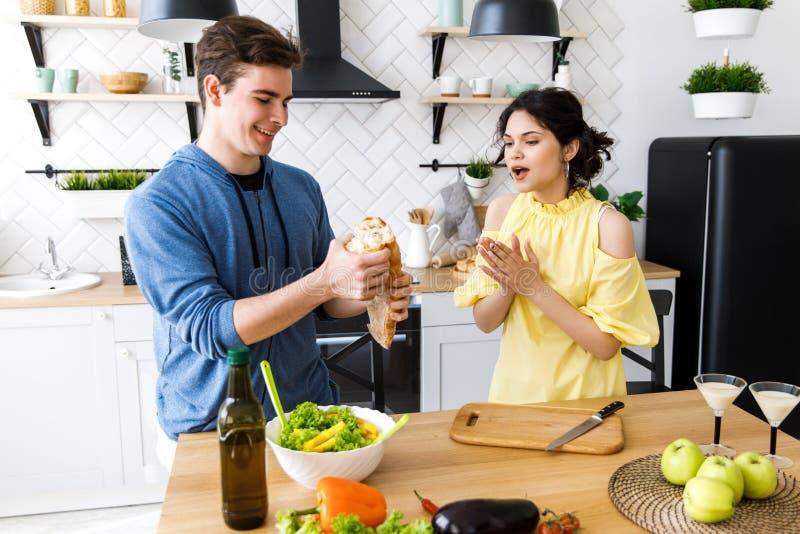 Jeunes couples de sourire mignons faisant cuire ensemble à la cuisine à la maison Un jeune, bienveillant couple mangeant la bague photos libres de droits