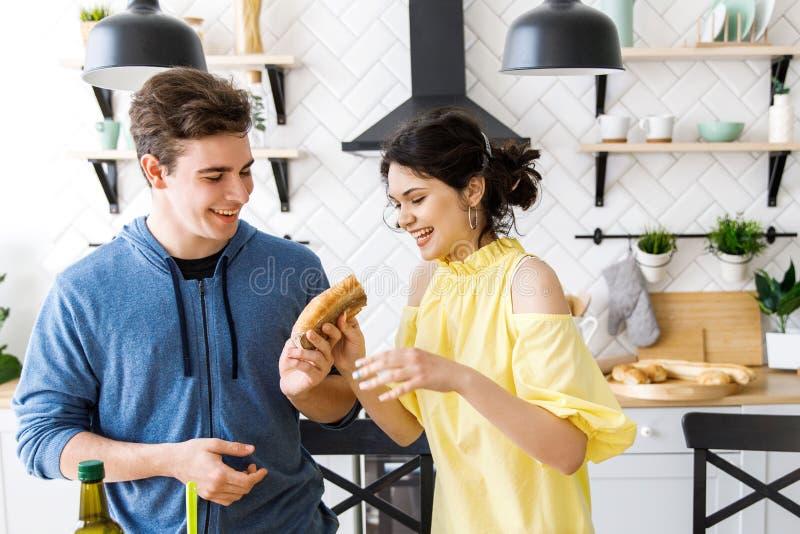 Jeunes couples de sourire mignons faisant cuire ensemble à la cuisine à la maison Un jeune, bienveillant couple mangeant la bague photographie stock