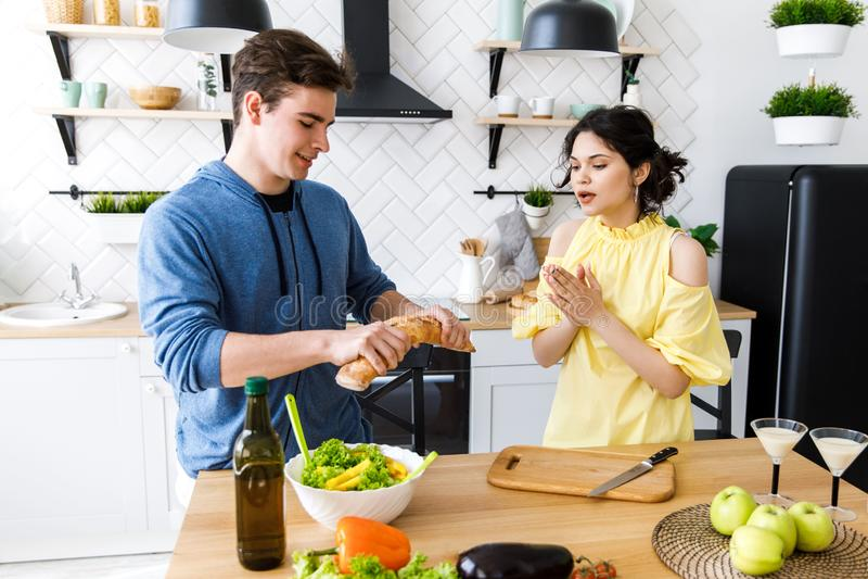 Jeunes couples de sourire mignons faisant cuire ensemble à la cuisine à la maison Un jeune, bienveillant couple mangeant la bague image stock