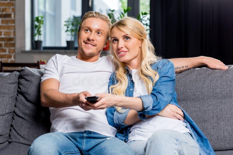 jeunes couples de sourire regardant la TV ensemble photographie stock