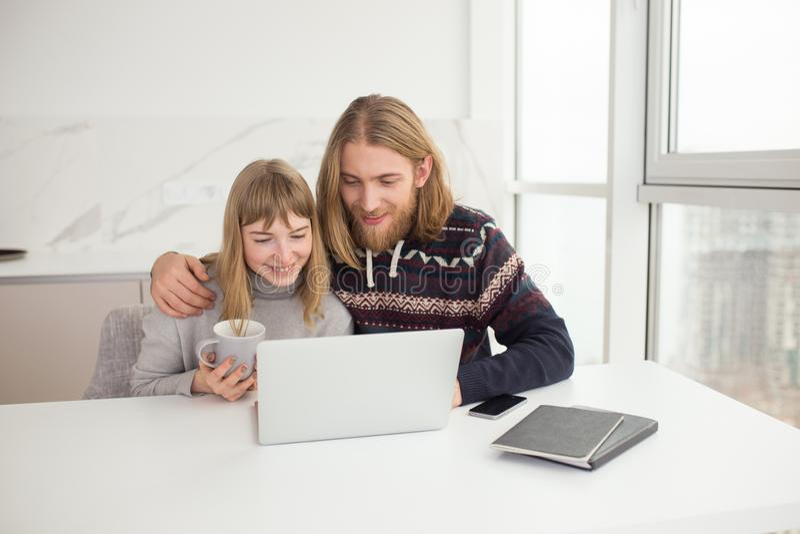 Jeunes couples de sourire se reposant ainsi que la tasse et l'ordinateur portable à la maison images libres de droits