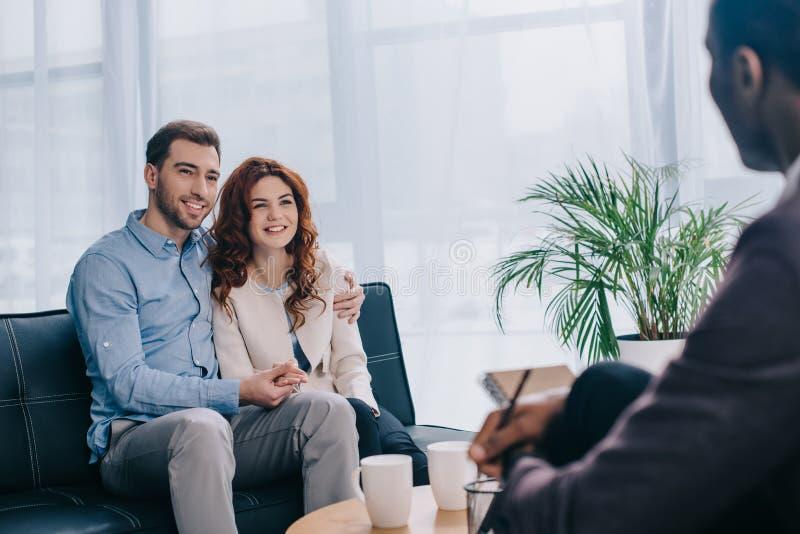 Jeunes couples de sourire se reposant sur le sofa et parlant au conseiller avec le crayon image libre de droits