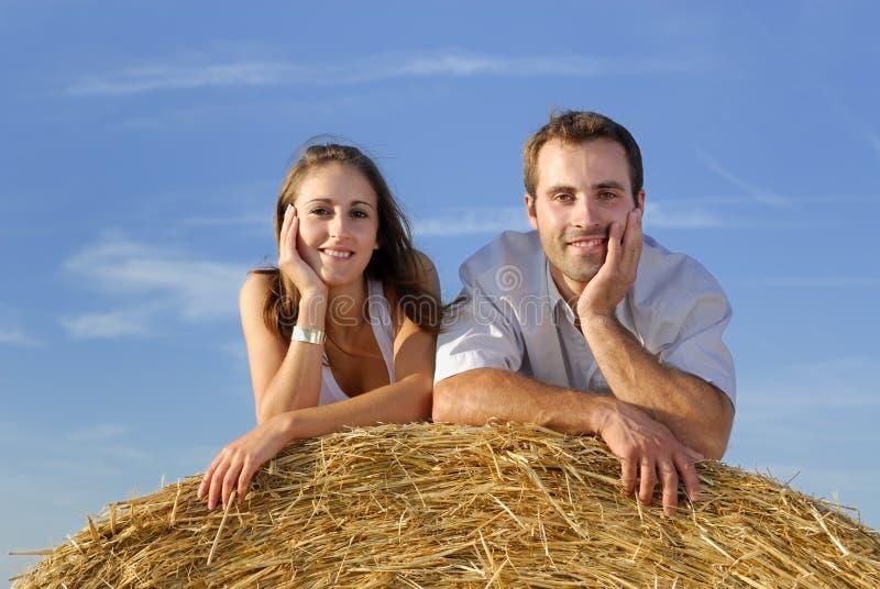 Jeunes couples de sourire se trouvant sur une balle de paille photographie stock libre de droits