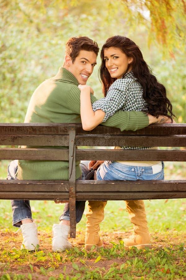 Jeunes couples de sourire sur un banc de parc image stock