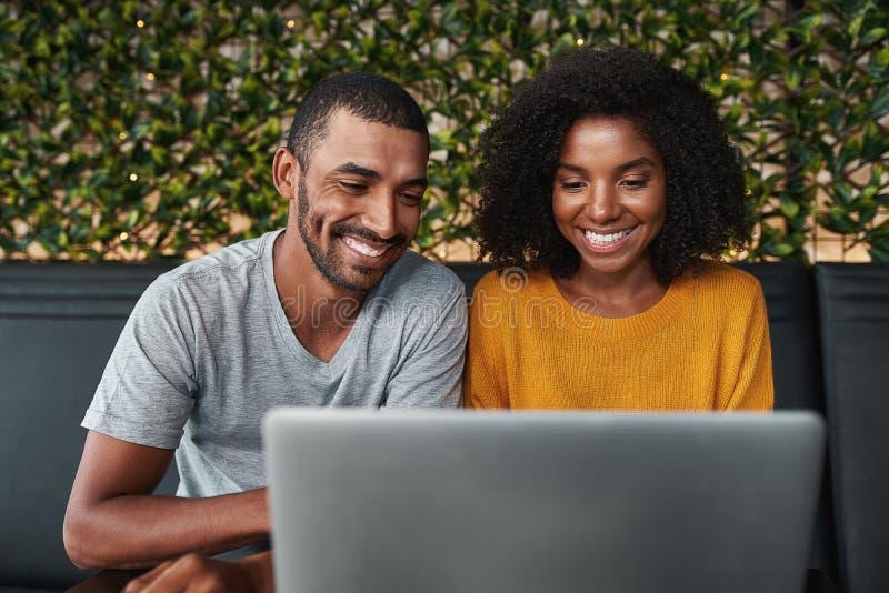 Jeunes couples de sourire utilisant l'ordinateur portatif photographie stock