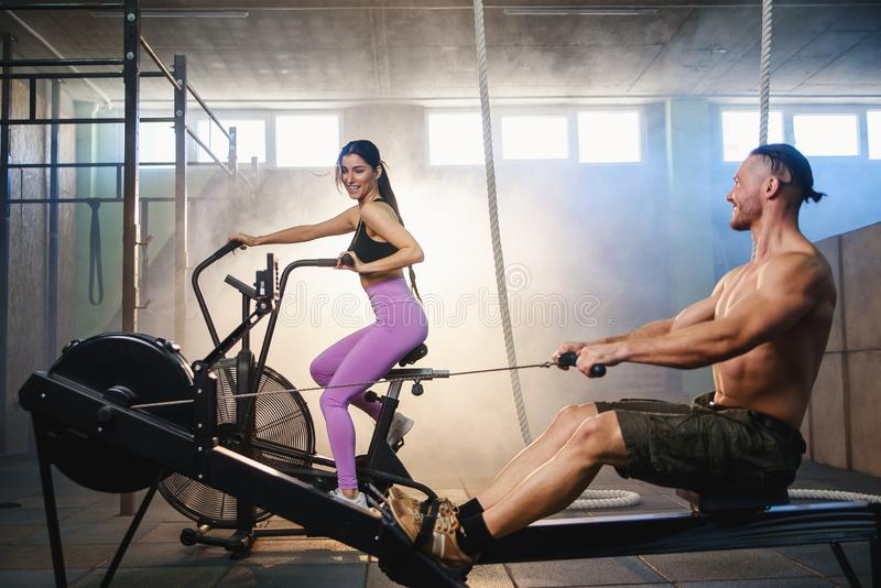 Jeunes couples de sport faisant des exercices sur les simulateurs dans le gymnase photo stock