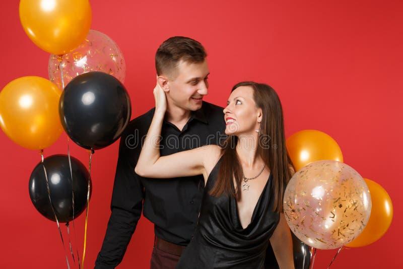 Jeunes couples de stupéfaction dans des vêtements noirs célébrant la fête de vacances d'anniversaire sur les ballons à air rouges images libres de droits