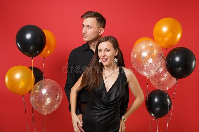 Jeunes couples de stupéfaction dans des vêtements noirs célébrant la fête de vacances d'anniversaire sur les ballons à air rouges image libre de droits
