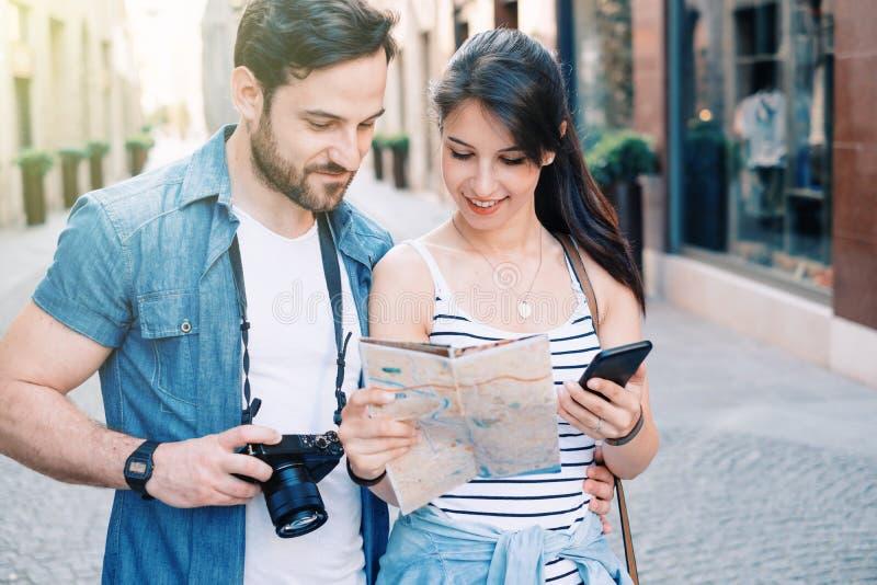 Jeunes couples de touristes dans la ville de visite de rue photographie stock libre de droits