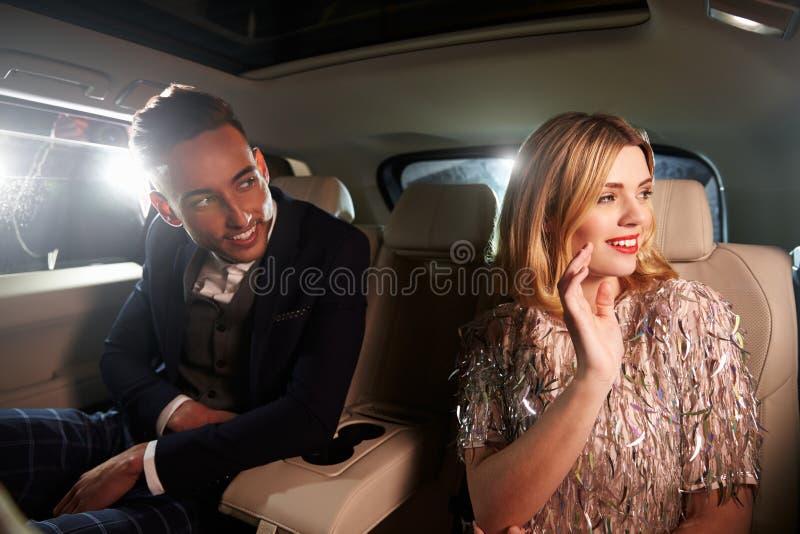 Jeunes couples derrière une limousine regardant hors de la fenêtre photographie stock
