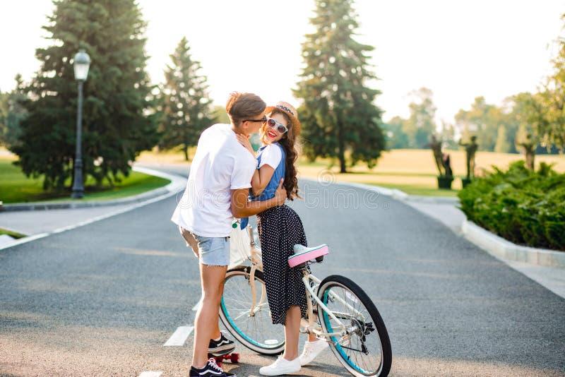 Jeunes couples des personnes romantiques sur la route sur le coucher du soleil La jolie fille avec de longs cheveux bouclés dans  images stock