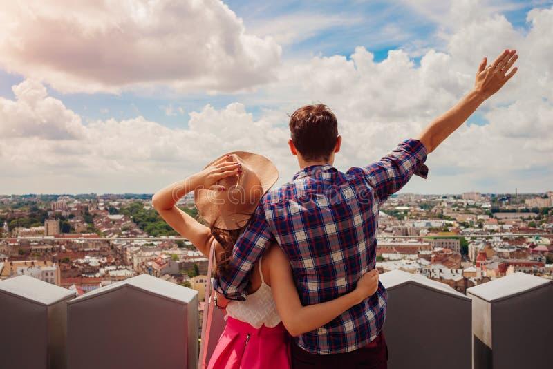 Jeunes couples des touristes avec les mains augmentées regardant sur Lviv, Ukraine de point de vue photo libre de droits