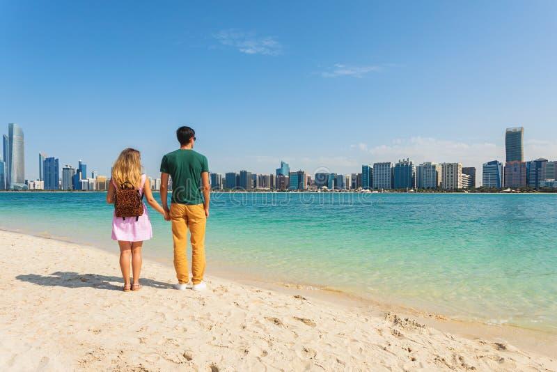 Jeunes couples des touristes tenant des mains sur la plage regardant les bâtiments modernes d'Abu Dhabi images stock