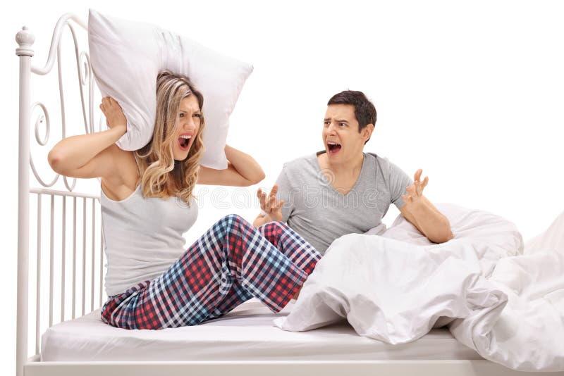 Jeunes couples discutant dans le lit images stock