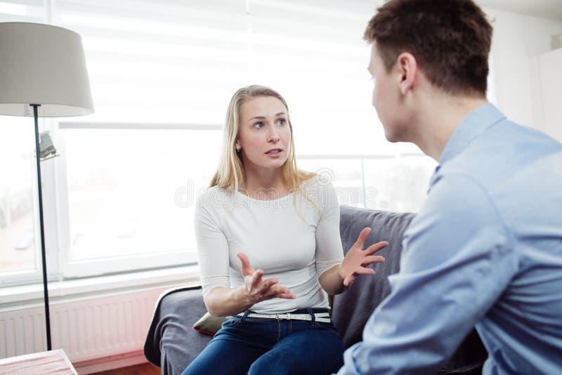 Jeunes couples discutant dans leur salon photo libre de droits