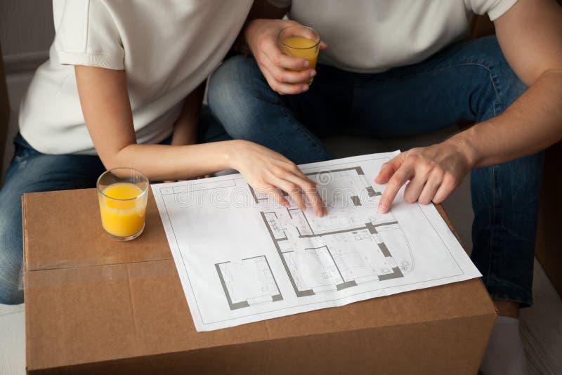 Jeunes couples discutant la fin de plan architectural de maison  images stock