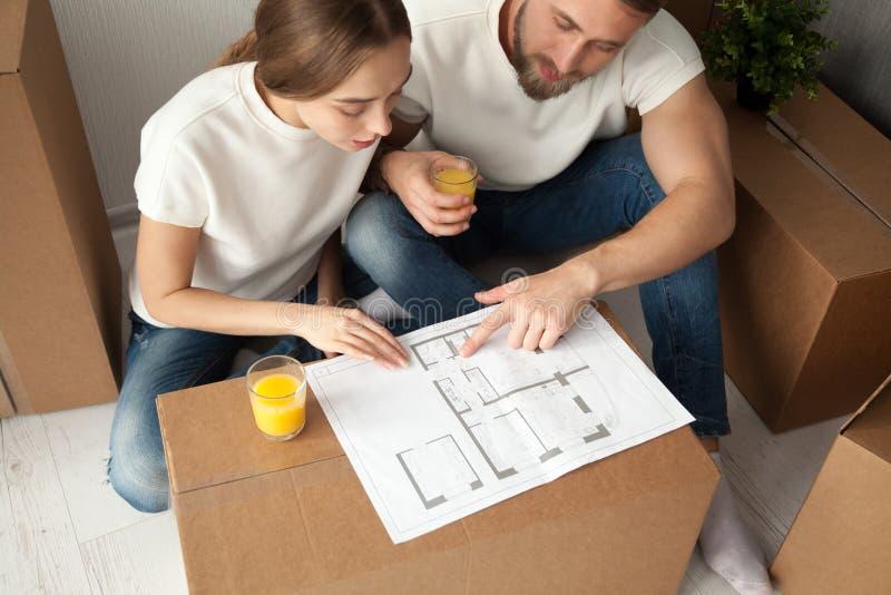 Jeunes couples discutant la vue supérieure de plan architectural de maison image stock