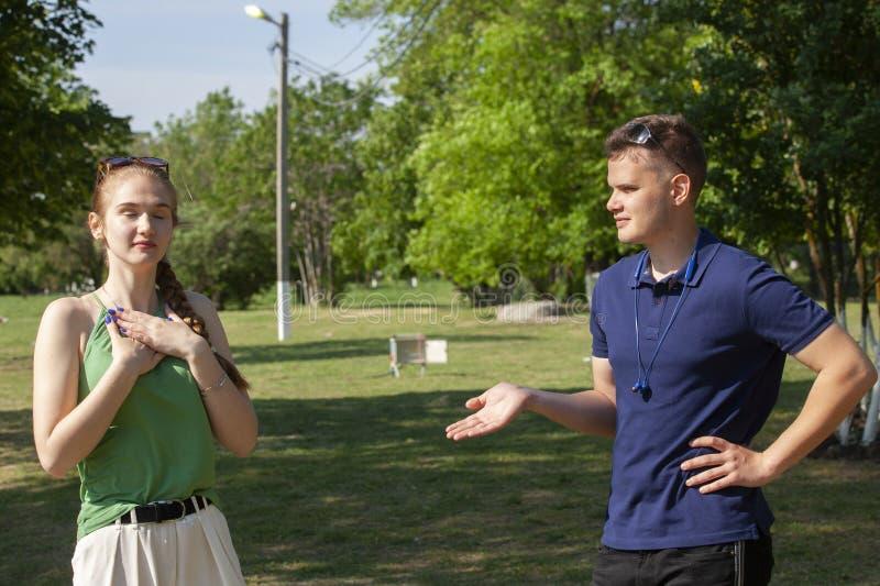 Jeunes couples discutant tout en se reposant sur le banc en parc Probl?mes dans les relations image stock