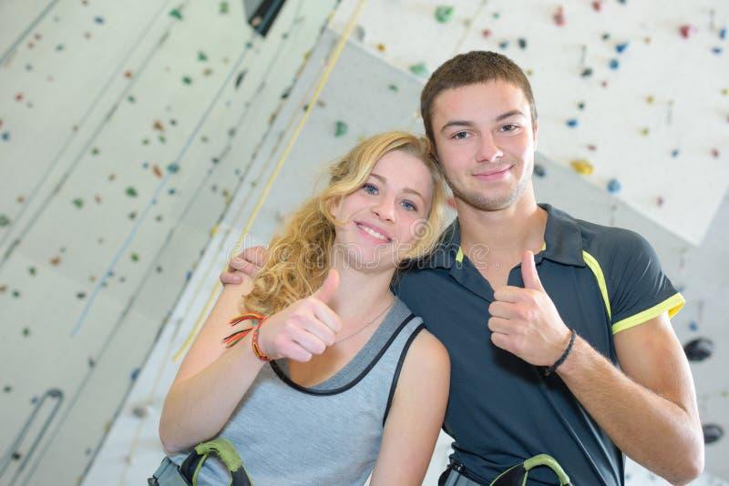 Jeunes couples donnant des pouces dans le mur s'élevant avant image stock