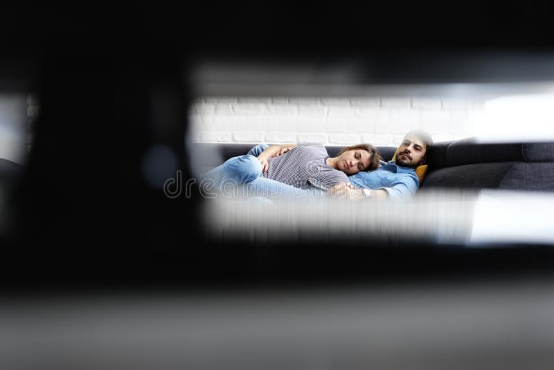 Jeunes couples dormant sur Sofa While Watching TV image libre de droits