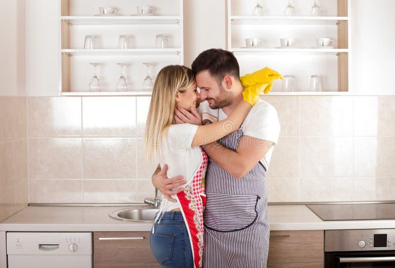 Jeunes couples embrassant après les travaux domestiques image stock