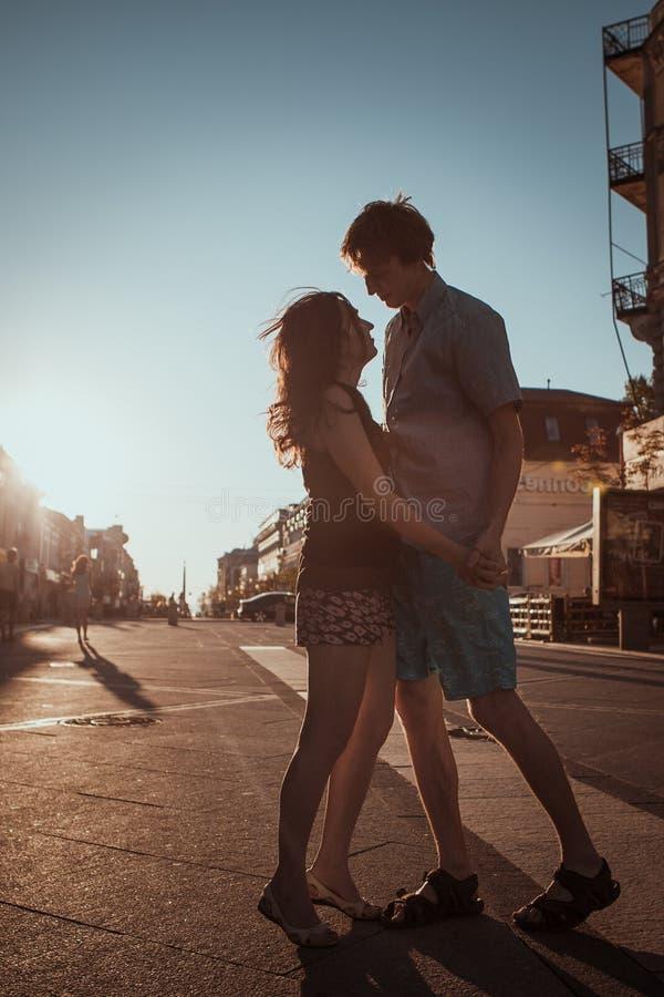 Jeunes couples embrassant au-dessus du coucher du soleil images stock