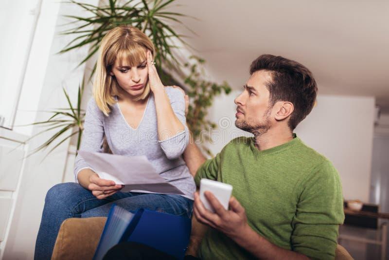 Jeunes couples embrassant et calculant les factures ? la maison photos stock