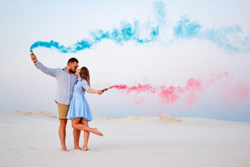 Jeunes couples embrassant et tenant la fumée colorée dans des mains, les ajouter romantiques à la couleur bleue et la bombe fumig images stock