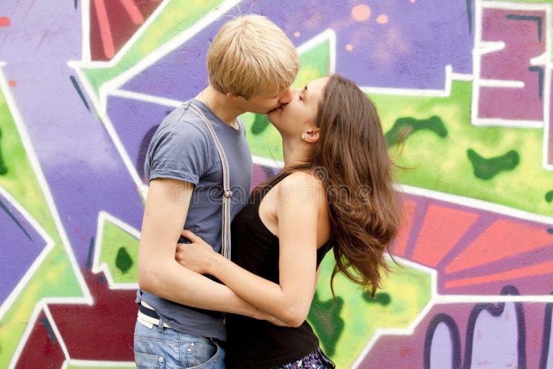 Jeunes couples embrassant près du fond de graffiti. photographie stock