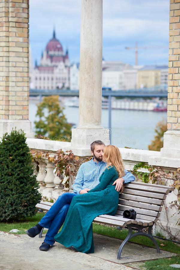 Jeunes couples embrassant sur le banc près des colonnes de Budapest photographie stock libre de droits