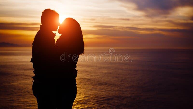 Jeunes couples embrassant sur le coucher du soleil vers la mer images libres de droits