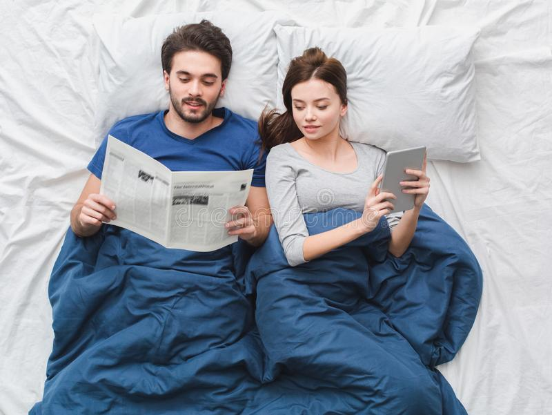 Jeunes couples en journal de lecture de type de concept de matin de vue supérieure de lit tandis que fille utilisant le comprimé  images libres de droits