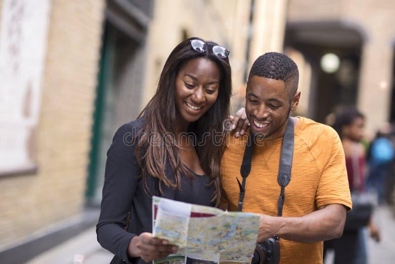 Jeunes couples en vacances avec une carte photos stock